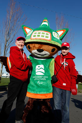 Two people posing with Paralympic mascot Sumi