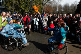 Torchbearer 15 (L) passes the flame to Torchbearer 16 (R) in UBC, BC