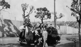 Group posing with automobile