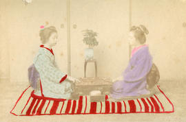 [Studio portrait of two women in traditional Japanese dress kneeling on the floor playing a game]