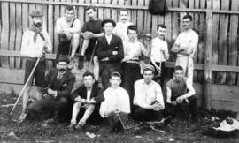 [Group of young men with lacrosse equipment in front of a fence]
