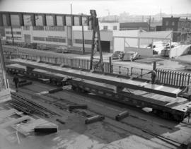 [Men loading large metal structure onto a Canadian Pacific Railway freight car at Western Bridge ...