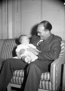 [Portrait of A.G. Duncan Crux holding a baby]