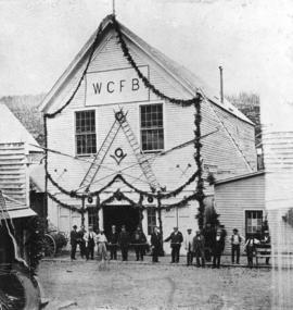 [The Williams Creek Fire Brigade crew in front of the fire hall decorated for Governor Anthony Mu...