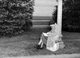 [Woman sitting on box waiting to see King George VI and Queen Elizabeth]