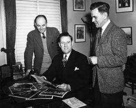 Ivan Ackery seated at desk looking at photographs with two men