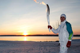 Day 62 Torchbearer 2 Jeff England carries the flame at sunrise in Barrie, Ontario.