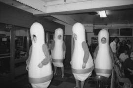 Four people dressed in bowling pin costumes