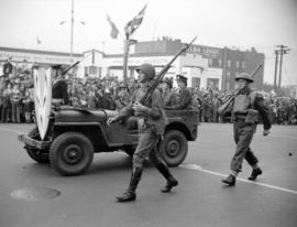 [Soldiers walking beside a jeep carrying military personnel in a military parade along Burrard St...