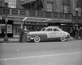 "[Black's Motors Ltd. car with banner advertising ""Mr. Blandings Builds his Dream House""..."