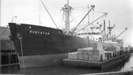 S.S. Rubystar [at dock, with lumber-filled barges alongside]