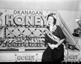 Miss P.N.E., Lynn Adcock, posing with display of Okanagan honey