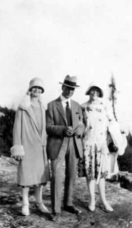 [L.D. Taylor standing on rocks with two unidentified women]