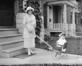 [Young woman with a child in a push cart standing in front of a house]