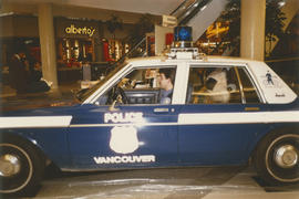 Tillicum and police officer inside police car in a shopping mall