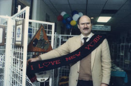 Mike Harcourt holding up a scarf in front of gift display