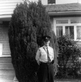 [Man in police uniform in front of house]