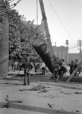 Men using crane and pulleys to erect Lumberman's Arch on Pender Street near Hamilton Street, for ...