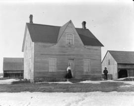 [Man and woman standing in front of farmhouse]