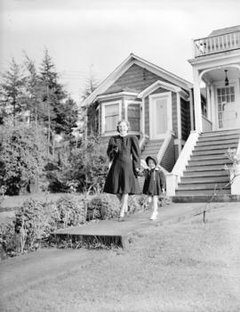 Georgina Brooksbank and child in front of houses