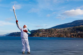 Day 89 Torchbearer 65 Adam Medrek carries the flame on to a frozen lake in Lake Country, British ...