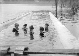[Women and girls swimming near shore of lake or river]