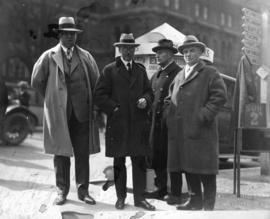 [Mayor L.D. Taylor standing with three men on sidewalk downtown in front of advertisement for Elk...