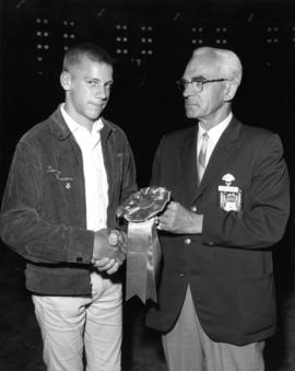 J. Grauer presenting young man with ribbon