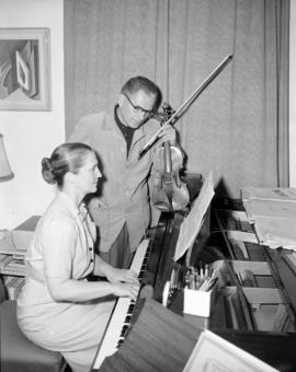 [Man with violin watching a woman play the piano]