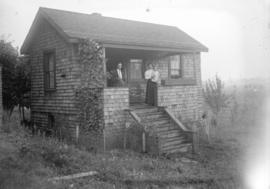 [Man, woman and child on front porch of house in Grandview-Cedar Cottage area]