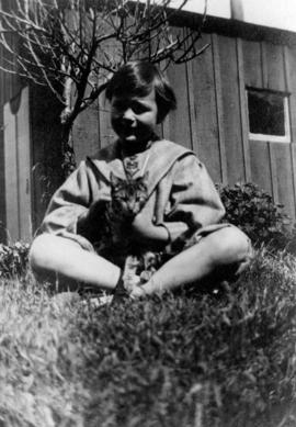 [Kenneth Taylor holding cat in yard]