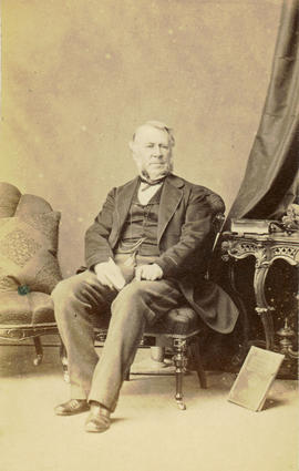 [Seated studio portrait of man, showing chairs and table]