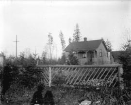 [View of house and yard behind fence]