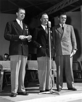P.N.E. President H.M. King, director T.R. Fyfe, and Forum Manager D. Dauphinee on stage addressin...