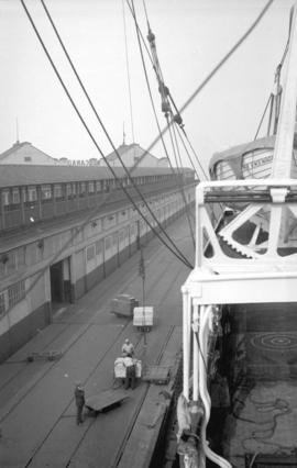 "[Men using cranes to load boxes onto Canadian-Australasian Royal Mail Line ship ""Niagara""]"
