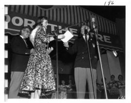 P.N.E. President W.J. Borrie presents envelope to the winner of Miss P.N.E. 1956, Joan Greenwood ...