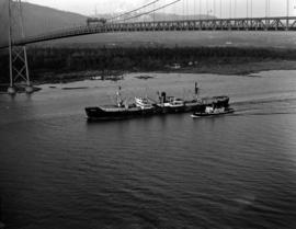 "[The cargo ship ""Seven Oaks Park"" accompanied by the ""Commodore"" passing unde..."