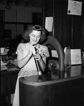 [Woman sending item through the pneumatic tube delivery system at Kelly Douglas Ltd.]