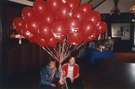 Two women holding Canada Festival balloons indoors at the Brockton Clubhouse