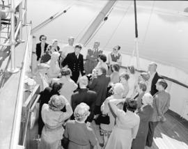 "Capt. Caldwell lectures [to a group of passengers] on bridge of ""Prince George"""