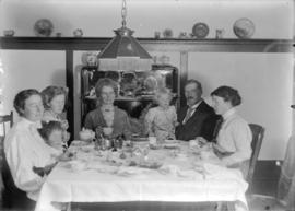 Women, children and man sitting around a dinner table