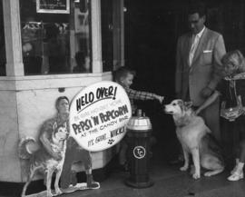 Ivan Ackery with [Nikki the wonder dog] and children in front of theatre building