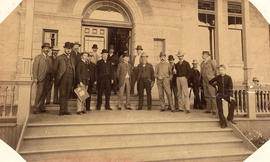 Group of men on steps at entrance to building