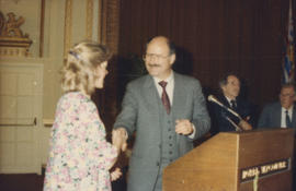 Mike Harcourt shakes hands with unidentified woman at podium