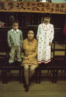 Mrs. King Fong Wong, former teacher at Mon Keang Chinese School, with two children