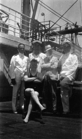 [L.D. Taylor and man in swim suit pose with officers aboard a ship]