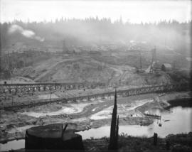[Upstream side of partially constructed Coquitlam Dam, showing construction camp in the distance.]