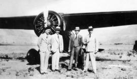 [Pilot Fletcher, Bill Templeton, A. McLachlan and Charlie Anstee in front of a high-wing Lougheed...