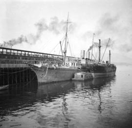 "[The first ship ""Empress of Japan"" at dock with another ship and a float containing mac..."