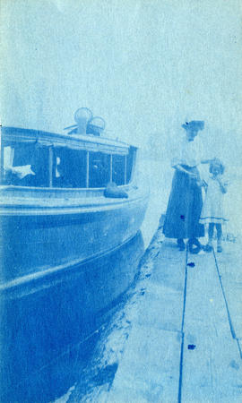 [Unidentified woman and girl on dock next to boat]
